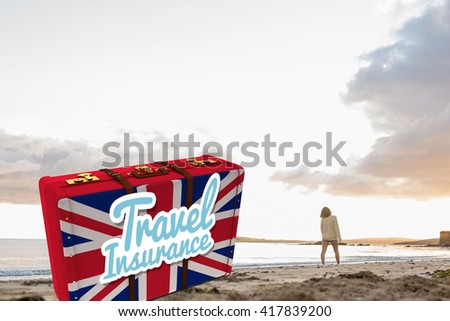 Woman in sweater walking on beach against travel insurance message on a british suitcase