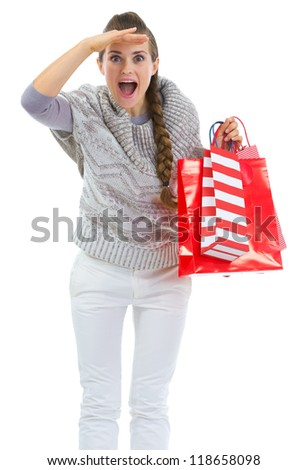 Woman in sweater with shopping bags looking into distance - stock photo