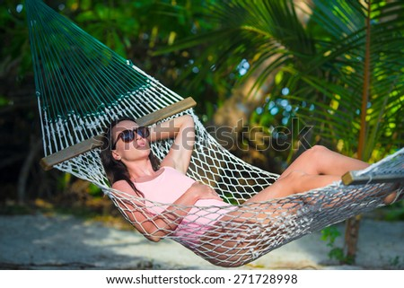 Woman in swimsuit relaxing on hammock sunbathing on vacation - stock photo