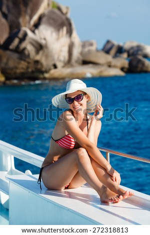 woman in swimsuit sitting on board  and looking to a sea