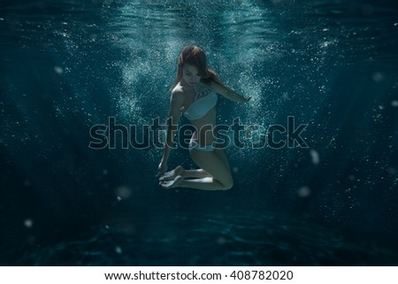 Woman in swimsuit swims under water among the light rays. - stock photo