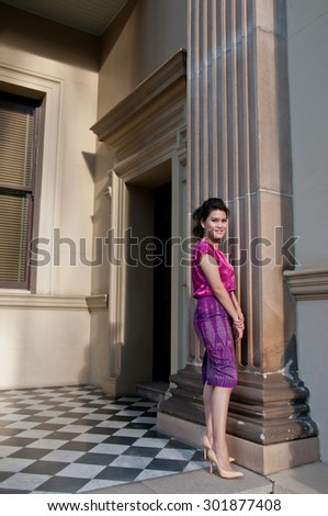 Woman in Thai silk traditional dress stand in old building