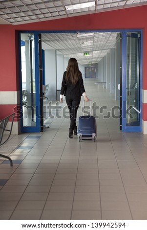 Woman in the airport with bag - stock photo