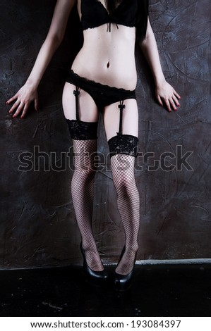 Woman in the black underwear standing at the wall wearing bra, panties, stockings and suspenders