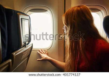 woman in the chair on board an airplane looking out the window