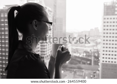 Woman in the city having a morning cup of coffee. - stock photo