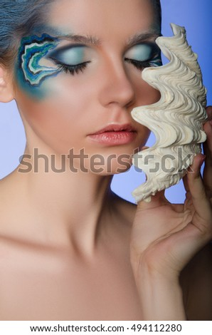 woman in the face-up mermaid on blue background