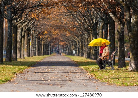 woman in the fall park with yello umbrella