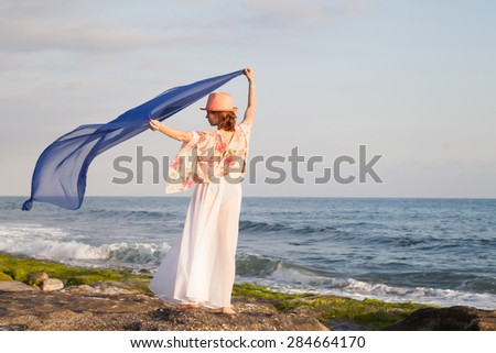 Woman in the hat posing on the beach - stock photo
