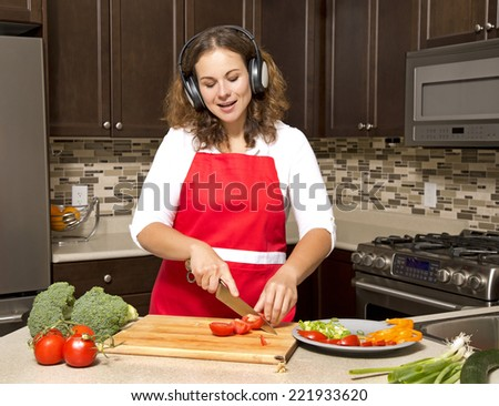 woman in the kitchen listening to music and cutting vegetables - stock photo