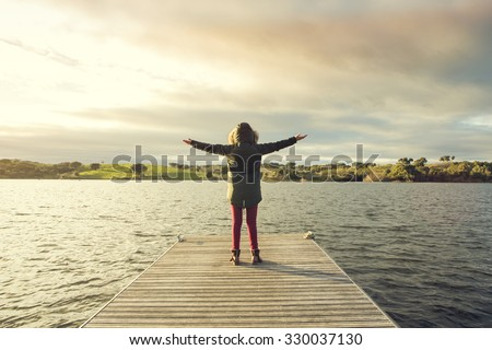 Woman in the lake with open arms at the sunset - stock photo