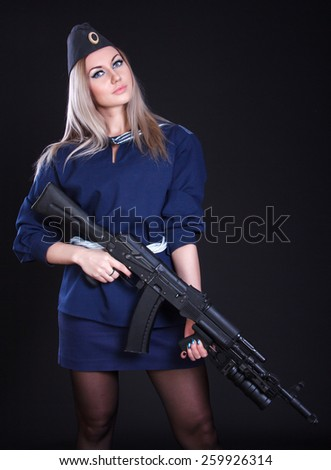 Woman in the marine uniform with an assault rifle over black background - stock photo
