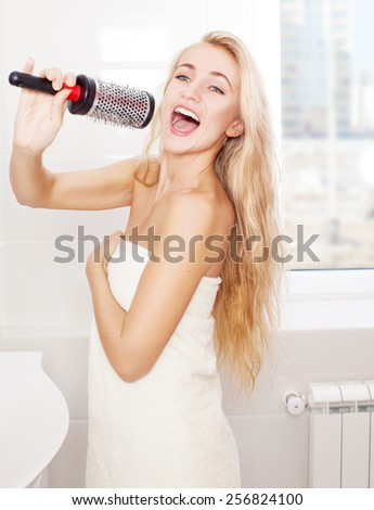 Woman in the morning at bathroom. Funny female sing song in comb - stock photo