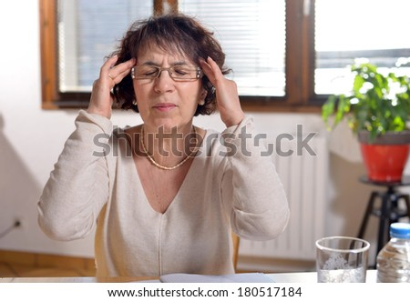 woman in the office has a headache and closes her eyes - stock photo
