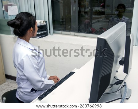 Woman in the office looking out the window. Medical staff in the office at night shift. The doctor is looking out the office window. Night shift at the hospital. Pause in hospital work. - stock photo