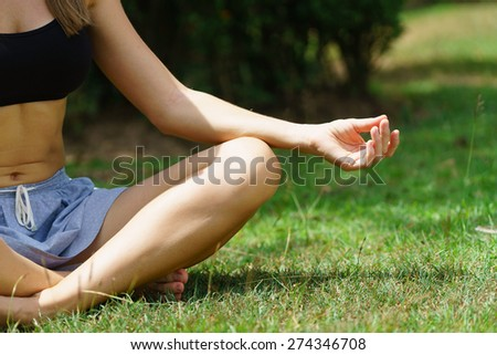 Woman in the park practicing yoga outdoors in the morning - stock photo