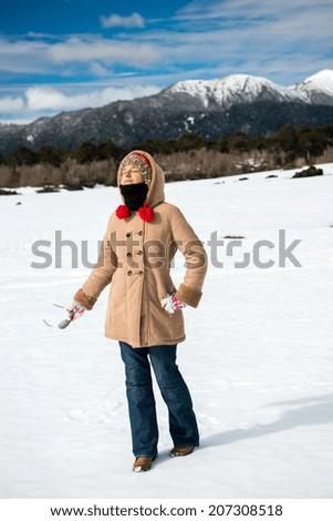 Woman in the snow enjoying the sun - stock photo
