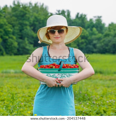 Woman in the straw hat  with basket strawberry in a field - stock photo