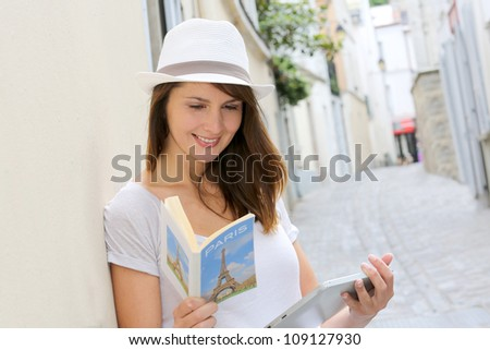 Woman in the street of Paris looking at tourist guide - stock photo