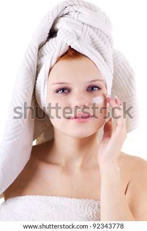 Woman in towel applying face cream isolated on white - stock photo