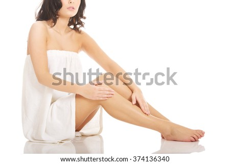 Woman in towel sitting on the floor.