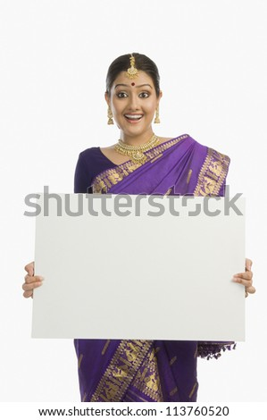 Woman in traditional Assamese dress holding a blank placard and smiling - stock photo