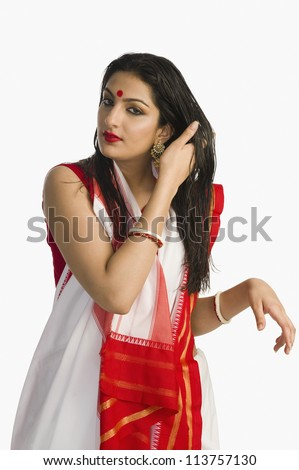 Woman in traditional Bengali saree with her hand in her hair - stock photo
