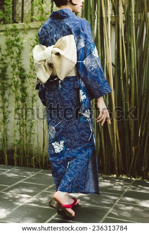 Woman in traditional Japanese kimono and geta shoes walking outdoors, rear view - stock photo