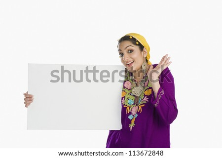 Woman in traditional Kashmiri dress holding a placard