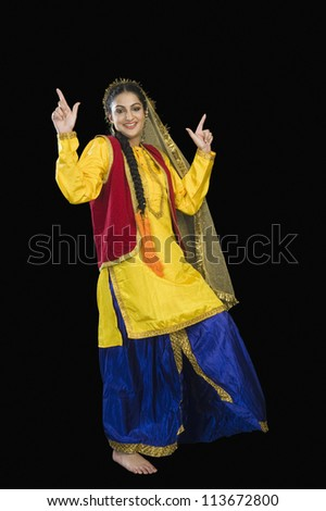 Woman in traditional Punjabi dress dancing - stock photo