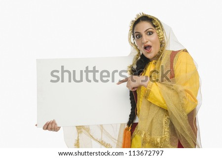 Woman in traditional Punjabi dress holding a placard