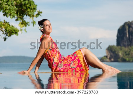 Woman in traditional thai summer dress enjoying travel and relax in Krabi, Thailand. Beautiful girl relaxing at poolside towards the sea during asian travel. - stock photo