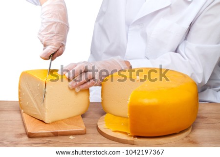 Woman in transparent gloves cutting kitchen knife a piece of cheese