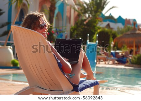 woman in tropical hotel with laptop - stock photo