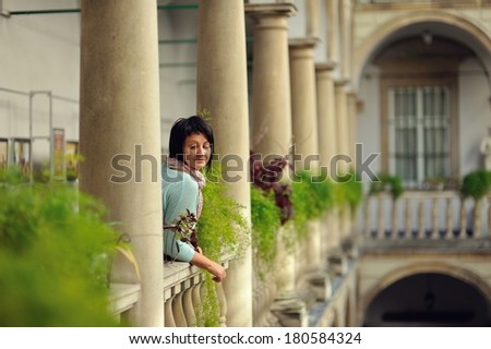 woman in trousers posing in antique balcony with stone pillars and railings - stock photo