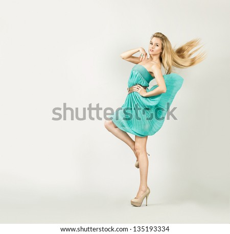 Woman in Turquoise Dress on Gray Backgound - stock photo