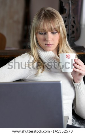 Woman in turtle-neck sweater holding mug of coffee