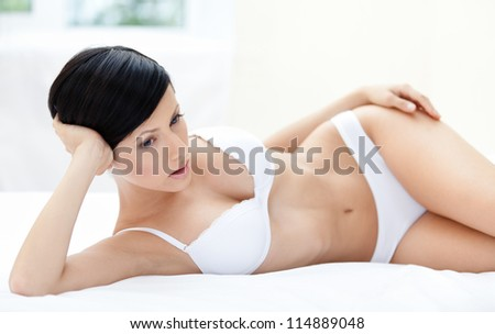 Woman in underwear is lying in the soft bed, white background - stock photo