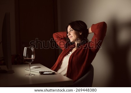 Woman in video call with a glass of wine on desk - stock photo