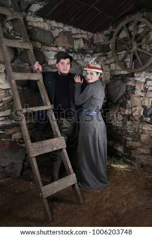 Woman in vintage dress and country style man inside village barn interior on stone wall background