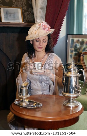 Woman in vintage dress and hat drinks tea in retro interior indoor