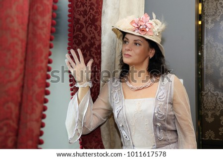 Woman in vintage dress and hat looks out the window waiting