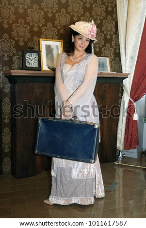 Woman in vintage dress and hat with old suitcase in hands