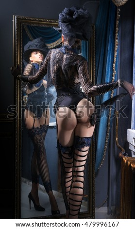 Woman in vintage lingerie, standing near the mirror, stroking himself a feather on the leg.