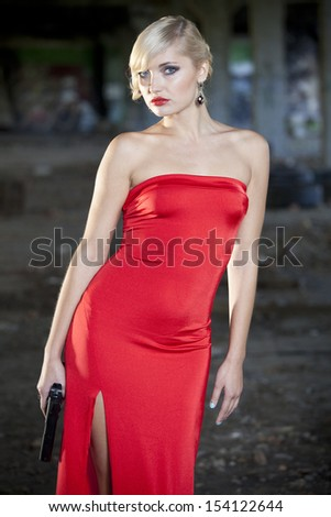 woman in vintage look holding a handgun in old fabric ruins - stock photo