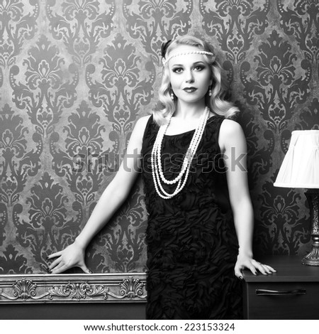 Woman in vintage room dress retro style. Professional make up and hairstyle. Black and white toned image - stock photo