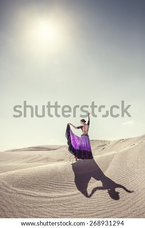 Woman in violet skirt dancing in the desert - stock photo