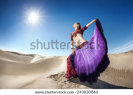 Woman in violet skirt dancing in the desert at blue sky - stock photo
