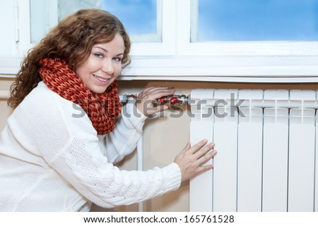 Woman in warm clothes checking the temperature of heating radiator in domestic room - stock photo