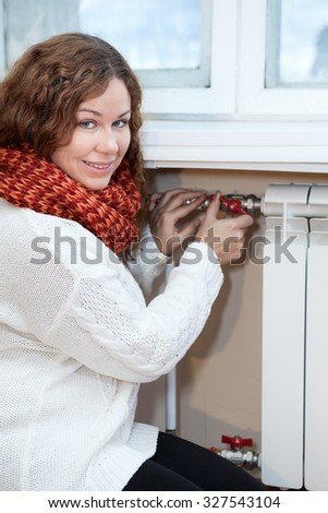Woman in warm clothes controlling the temperature of heating radiator in domestic room - stock photo
